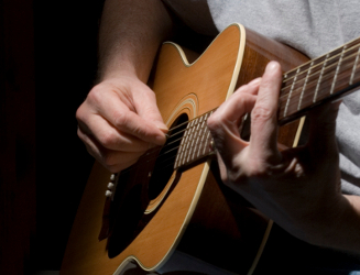 A guitar player forming a bar chord